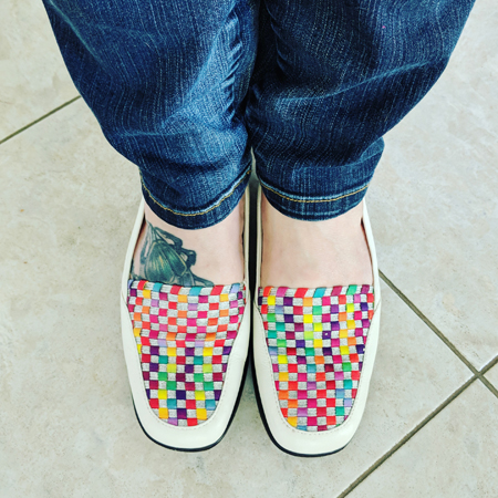 image of my legs from the knees down, clad in blue jeans, and my feet in white loafers featuring a colorful pattern on the top of the foot