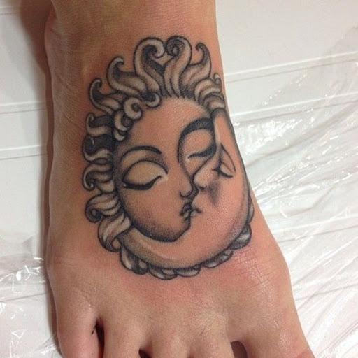 Este preto e cinza tatuagem mostra uma personificação do sol e da lua beijando e é representada na parte superior do utente de pé direito.