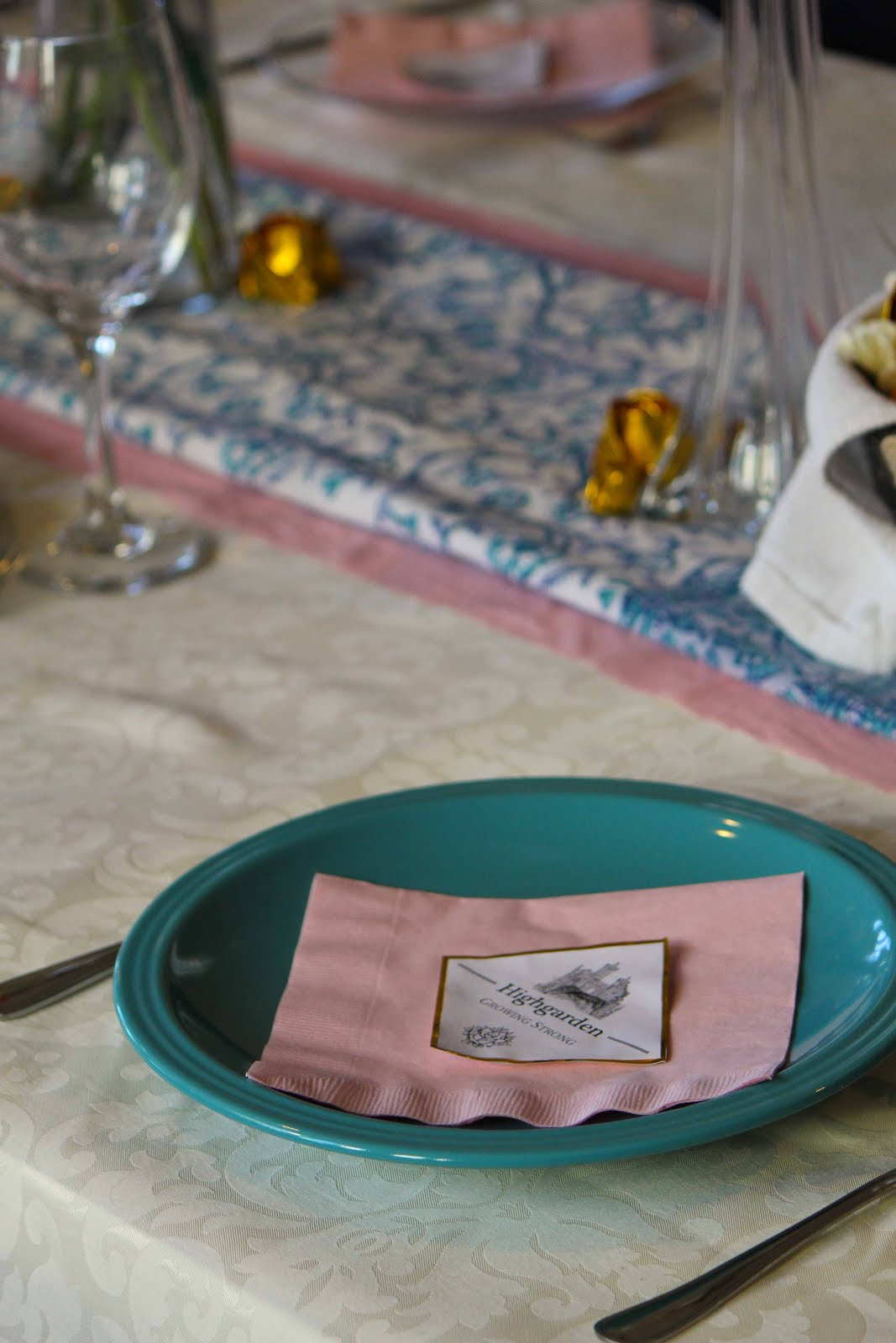 Place setting: turquoise plates, with white and gold menus and pink napkins
