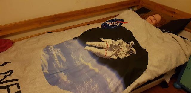 Pretend sleeping child under Astronaut NASA bedding