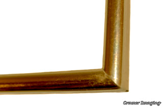 Cramer Imaging's photograph of a single gold colored metal picture frame corner on a white background