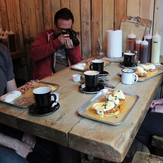 Brunch on trays on a wooden table. Photographer in back