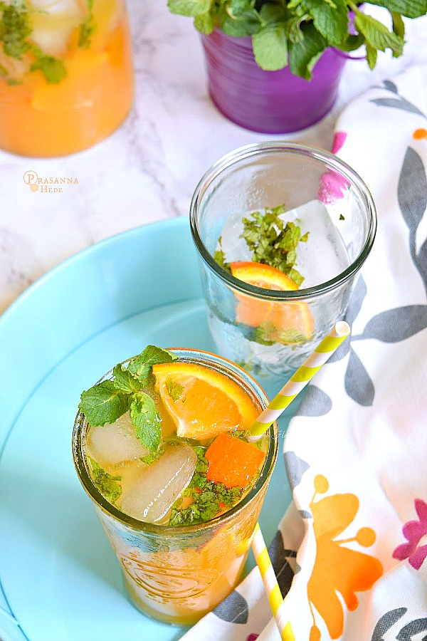 Non Alchholic Orange Mojito served in a blue tray with orange wedges,mint leaves and lots of ice