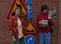 Simon y la candidata a volver novia de Sam mientras lee libros junto a carteles