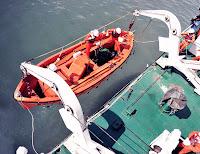 Bir gemide mataforaya asılı olan turuncu renkli bir filikanın suya indirilmesi