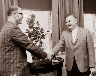 Tom Roos and President Kemeny shake hands in front of a small table with a potted lemon tree.