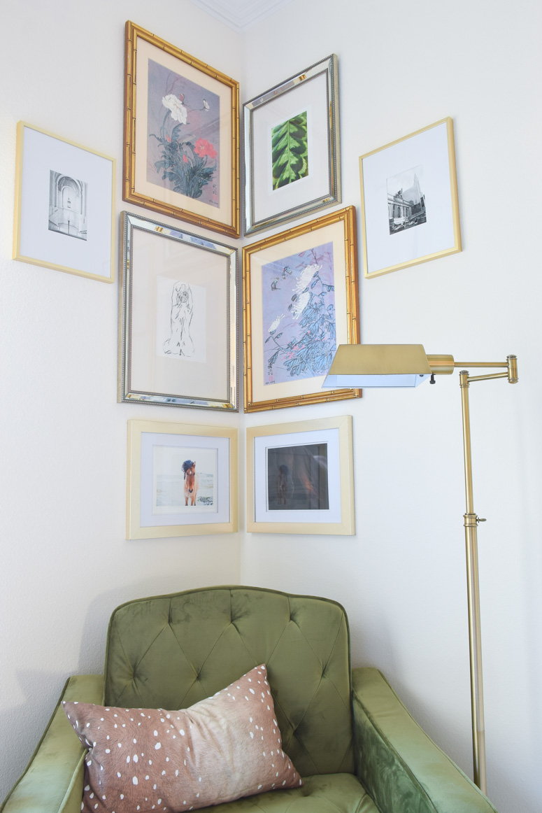 A beautiful silver and gold corner gallery wall in a reading nook in a master bedroom.