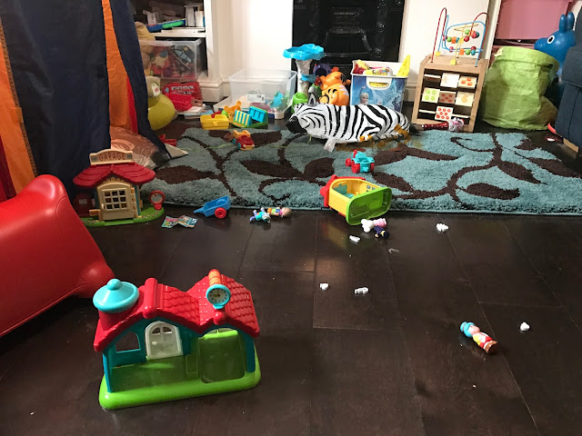 Dark brown wooden floors covered in assorted toys