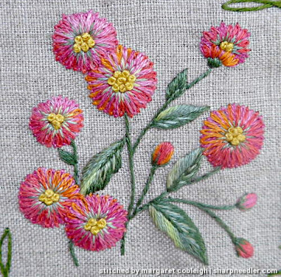 Details of floral motif with pink and orange flowers. Flowers are stitched with 2 layers of pink/orange House of Embroidery variegated threads.