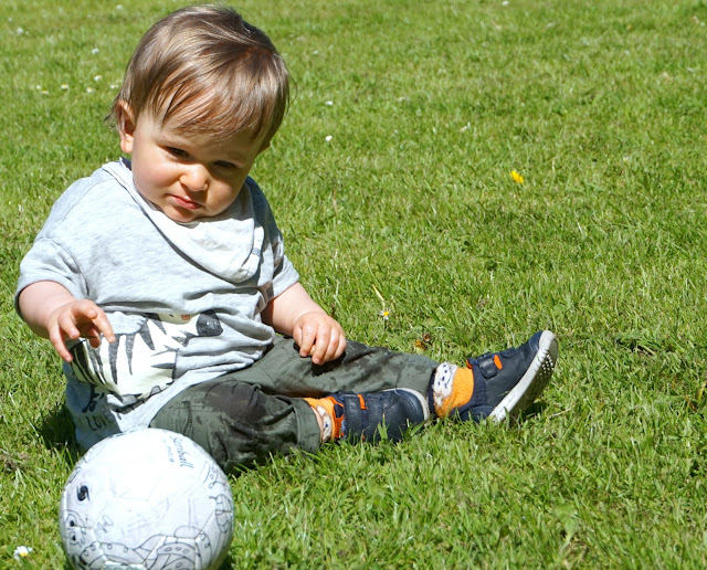 baby boy seated on grass and reaching for football