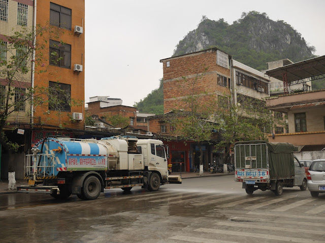 Pingfeng Hill (屏峰山) and water truck spraying water onto the road in Yunfu