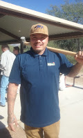 A man wearing a tan cap and a blue shirt holding a large sledge hammer - Chris from the Insectary.
