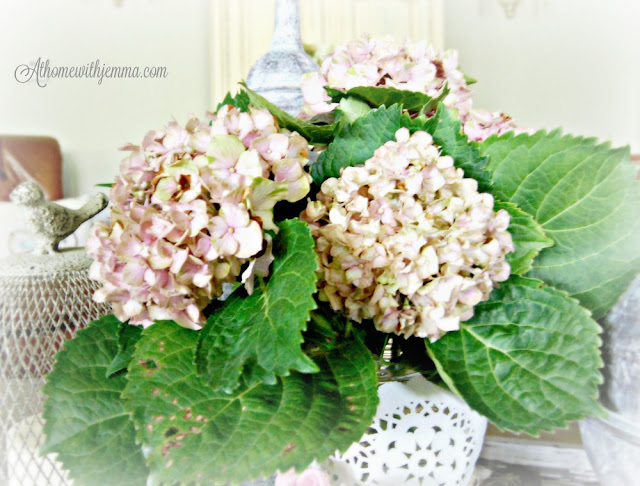Hydrangeas next to a vintage wire birdcage make a romantic vignette