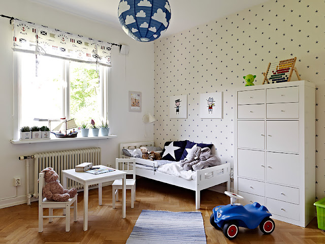 Child's room with one cream colored wall with blue poka dots, a white table and chair with a teddy bear in one of them, a toy car, a white bed with blue pillows, a white chest of drawers and a window with small plants on the window sill