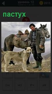 Мужчина около лошади с собакой в одежде пастуха на склоне небольшого холма в хорошую погоду