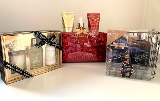 3 beauty gift sets including one in gold, one in a sparkly red bag and a men's set in a wire crate