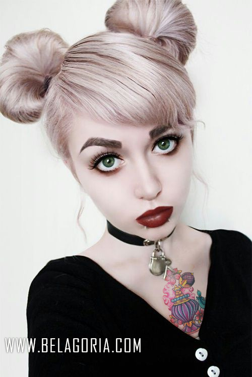 Vemos una chica jovencita, con el pelo recogido en dos moños, es gotica, lleva tatuado en el pecho una botella de perfume frances