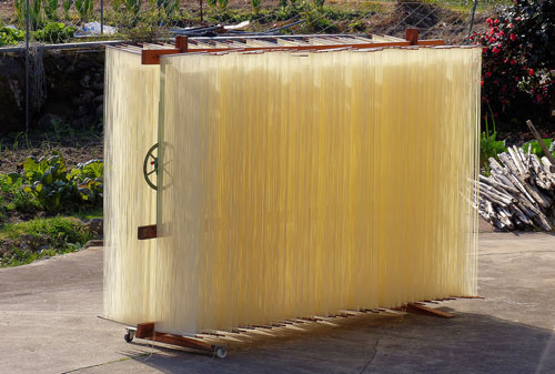 Somen noodles drying in the winter sun in front of a farmhouse.