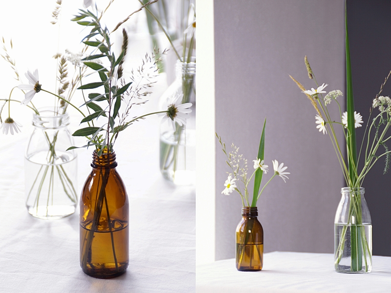 Schnelle sommerliche Tischdeko mit Margeriten, Giersch und Gräsern in braunen und klaren Vintage Glasflaschen, weißen Porzellan-Teelichtern und weißer Tischdecke | Tasteboykott