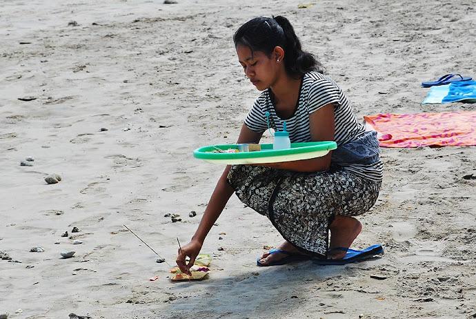 Mujer quemando incienso en la playa