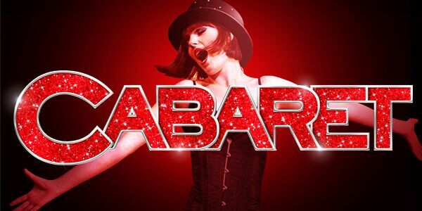 a woman in black corset and top hat sings with her arms outstretched behind red glitter letters spelling out cabaret