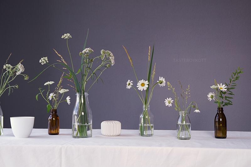 Sommerlich simple Tischdeko mit Margeriten, Giersch und Gräsern in Glasflaschen, Teelichtern und weißer Tischdecke | Tasteboykott
