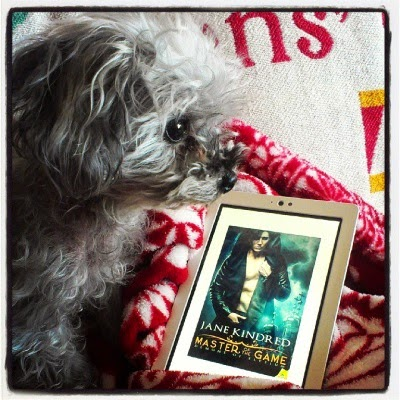 Murchie sits beside a white Kobo with Master of the Game's cover art on its screen. The blue-toned cover depicts a dark-haired, pale-skinned man wearing an open hoodie.