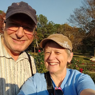 Chris and Betsy - As We Go standing in a rose garden
