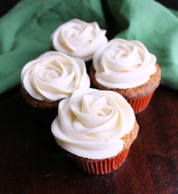 caramel buttercream roses on top of carrot cake cupcakes
