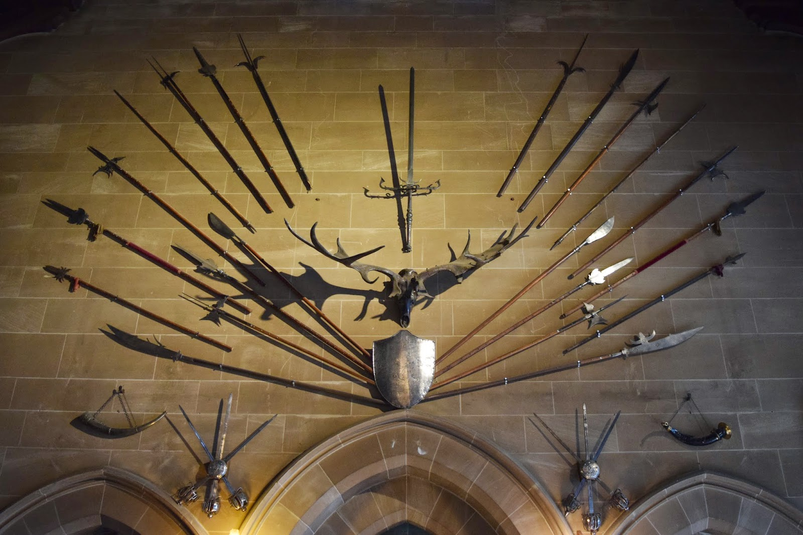 some of the weapons on display in the great hall at warwick castle