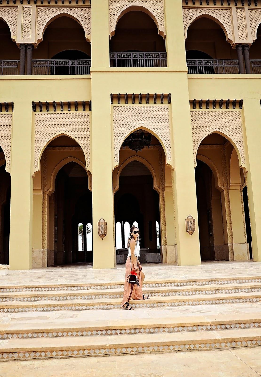 Whitney's Wonderland's Whitney Valverde Top International Luxury UK Travel Blogger shares the experience at Casablanca with EMU and Mazagan Beach Resort.  Whitney wears Kurt Geiger, Free people trousers, Superdry, and EMU Australia