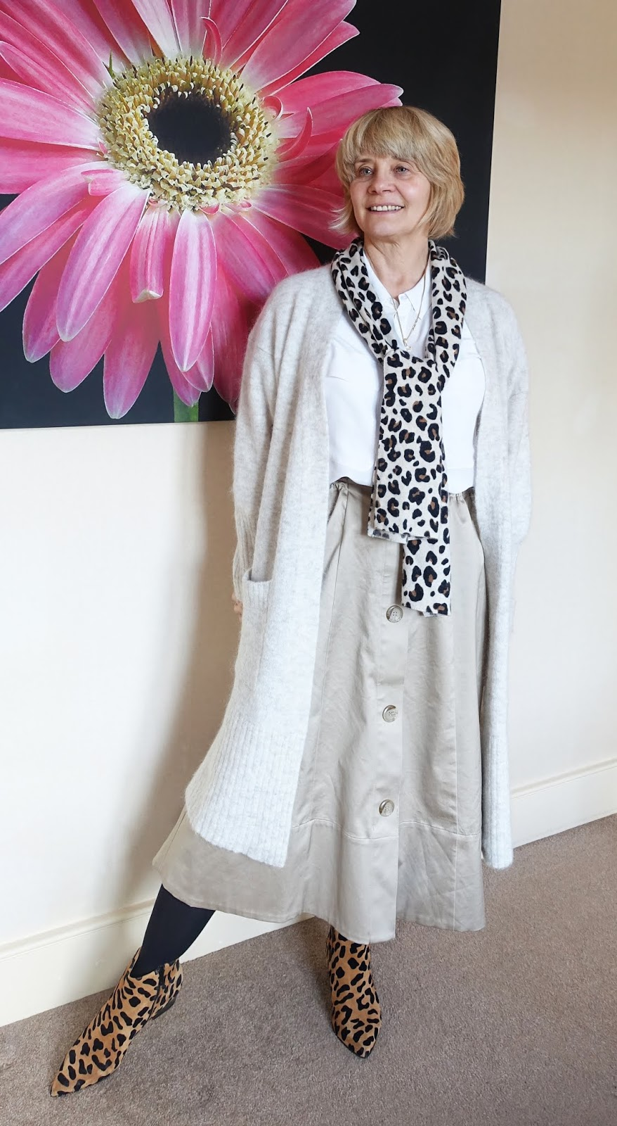 Adding a leopard print scarf lifts an outfit of fawn midi skirt, white blouse and long ivory cardigan