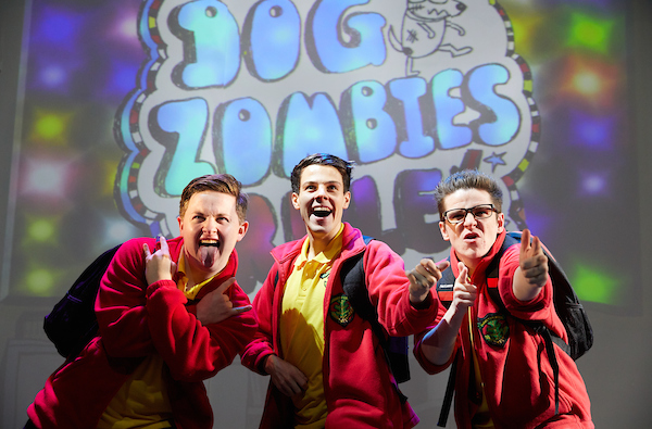The male cast of Tom Gates Live on Stage, posing in front of a Dog Zombies poster