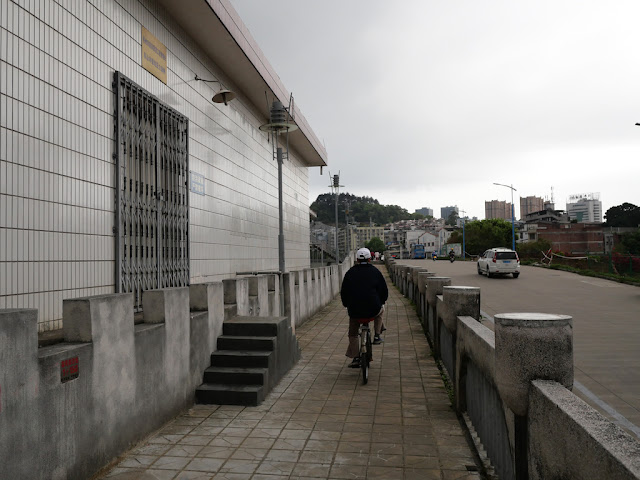 man riding a bike on a wall bordering the Gui River (桂江) in Wuzhou (梧州)