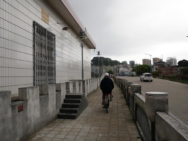 man riding a bike on a wall bordering the Gui River (桂江) in Wuzhou (梧州)