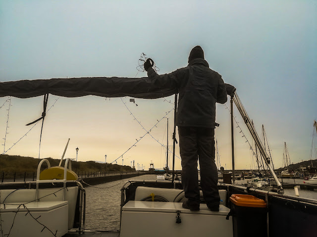 Photo of Phil taking down the fairy lights on Ravensdale's aft deck