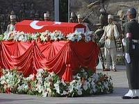 Beyaz çiçeklerle süslenmiş kırmızı bir katafalk üzerinde Türk bayrağına sarılı bir asker naaşı ve başında bekleyen asker