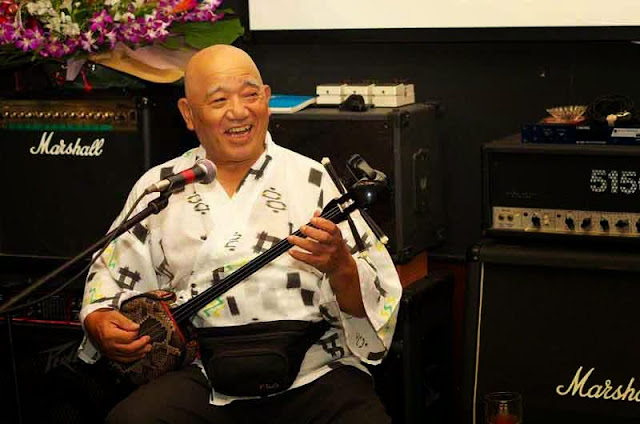 man playing sanshin and smiling