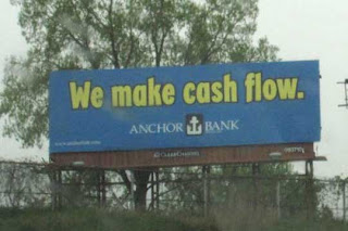 Blue billboard with yellow letters reading We make cash flow, Anchor Bank
