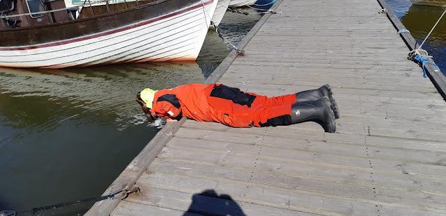 Henkilö makaa mahallaan laiturilla ja tähystää veteen.