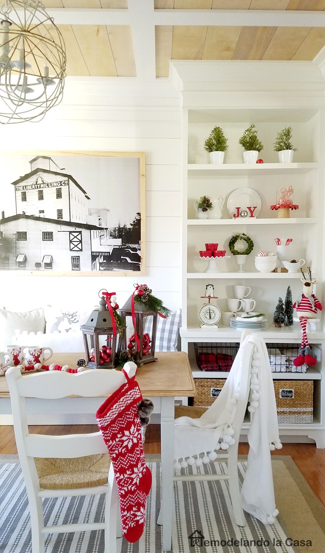 farmhouse dining table and lanterns filled with red ball ornaments.