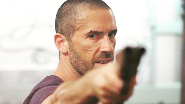 scott adkins with a shotgun