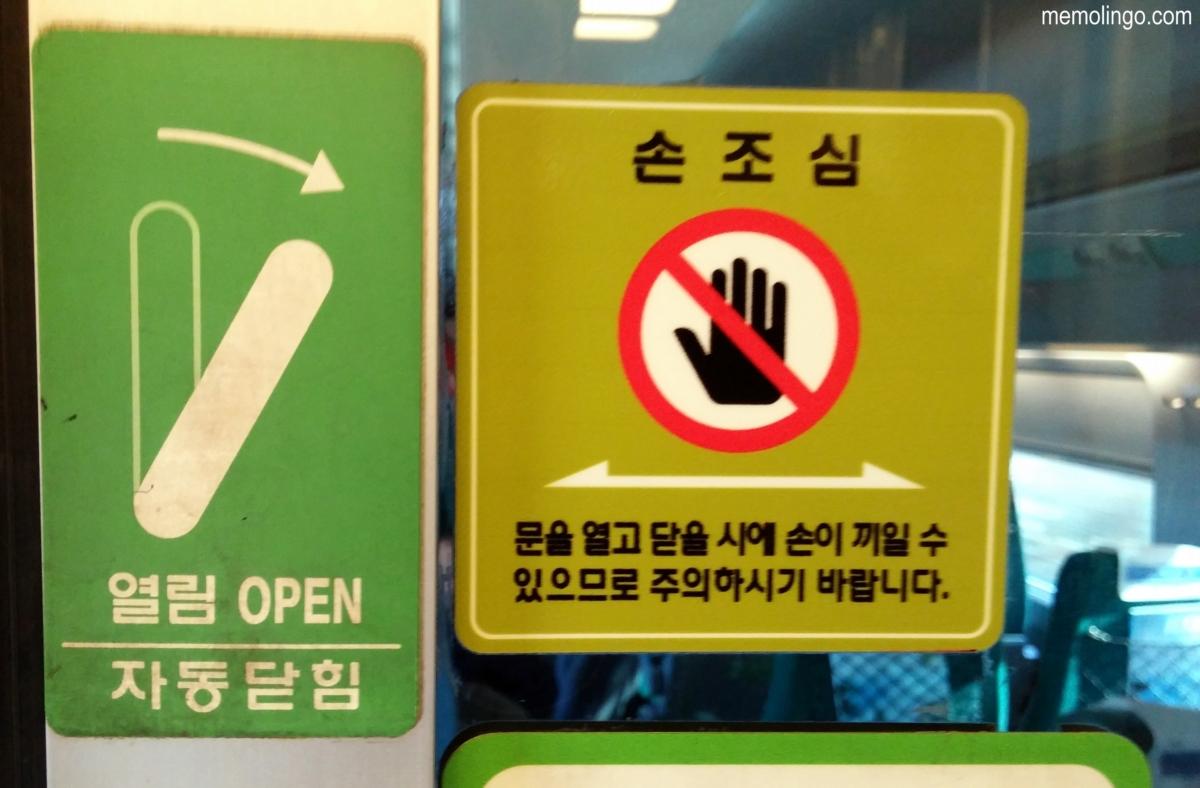 Carteles en coreano en las puertas entre vagones del tren KTX
