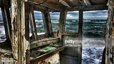 Φαίνεται η θάλασσα μέσα από το εσωτερικό ενός κατεστραμμένου πλοίου. Ακολουθεί το κείμενο: Έχουν τα όνειρα αλλόκοτη δύναμη  είναι του νου μυλόπετρες,  άλλης αλήθειας οντότητες σκοτεινές...  Τώρα που μοιάζει η ζωή να μικραίνει  μόνο η θάλασσα μένει,  εκνευριστικά ήρεμη...  Το σκουριασμένο του πλοίου κουφάρι  που βλέπω στον ύπνο μου κάθε βράδυ,  δοξασμένο παρελθόντος απομεινάρι  έχει στοιχειωμένη την κουπαστή,  την μπούμα κατεστραμμένη,  τον πίνακα οργάνων μισοσβησμένο...  Έχει από άγρια κύματα καταστραφεί  μετά από μιάν αγρία, υπέροχη μάχη  χιλιάδες λόγια κυμάτων λέει,  όπως η ιδία μου η σκληρή ζωή...