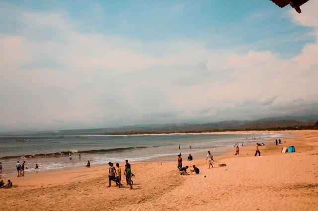 para wisatawan berjalan di pantai santolo