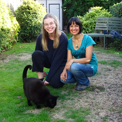 two women with black cat