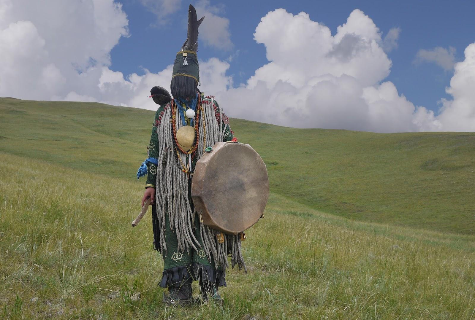 Outro xamã mongol, vestido dos pés à cabeça e portando um tambor