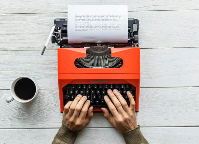 Person Holding Black and Orange Typewriter HD Copyright Free Image