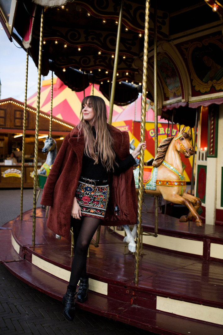 rust coloured teddy coat, embroidered skirt, buckle boots