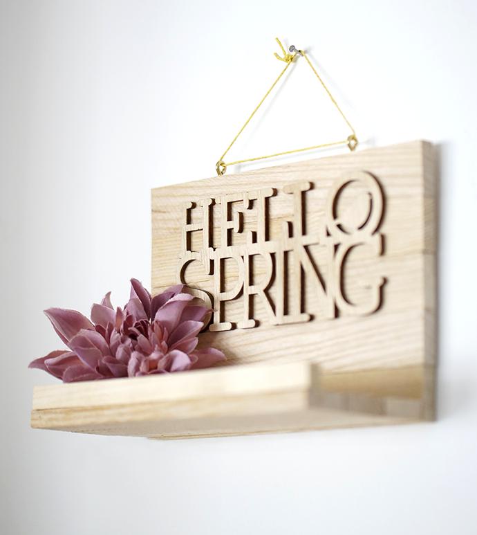 """Holzablage aus Stäbchenparkett mit dem Schriftzug """"Hello Spring"""" hängt an der Wand"""